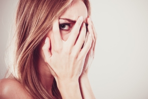 Afraid frightened woman peeking through her fingers